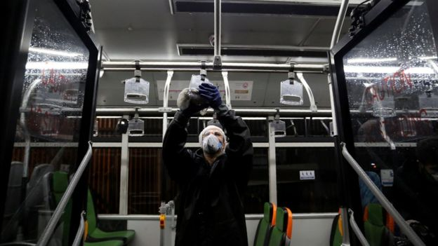 A worker cleans a bus in Teheran in an attempt to prevent the spread of the novel coronavirus