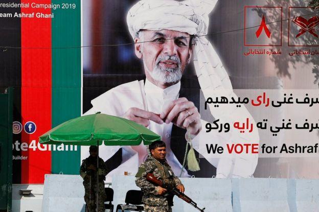 Anggota pasukan keamanan Afghanistan berdiri di depan poster kandidat presiden Afghanistan Ashraf Ghani di Kabul, Afghanistan 2 September 2019.