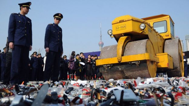 Local policemen and members of the public look on as the road roller crushes the counterfeit products on February 23, 2011 in Shanghai, China.