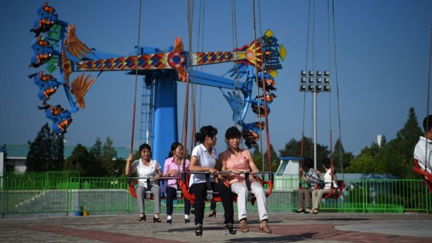 People enjoy rides at the Rungra People's Pleasure Park , Pyongyang