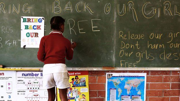A South African girl, shown writing on a chalkboard