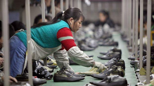 Mulher trabalha em fábrica de sapatos na China