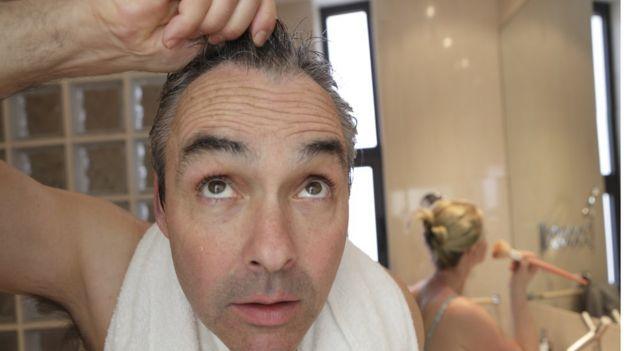 Hombre se toma el cabello con sorpresa mientras está en el baño.
