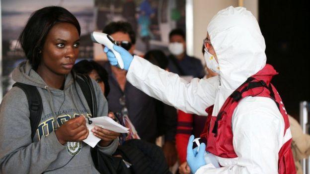 Agente de saúde medindo temperatura de uma mulher