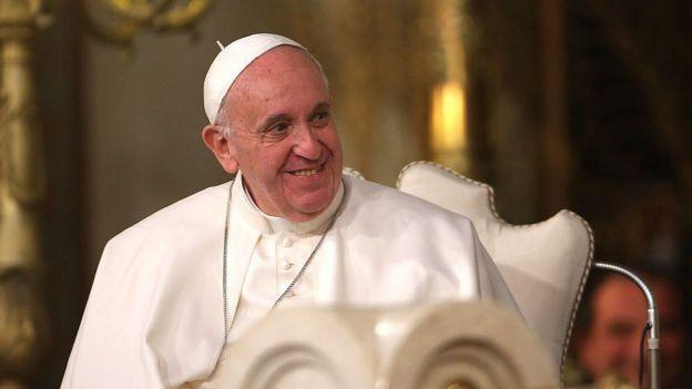 O Papa Francisco, com as vestimentas papais, senta em uma cadeira e sorri