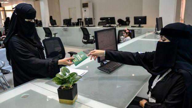 سيدة سعودية تمسك جواز سفرها