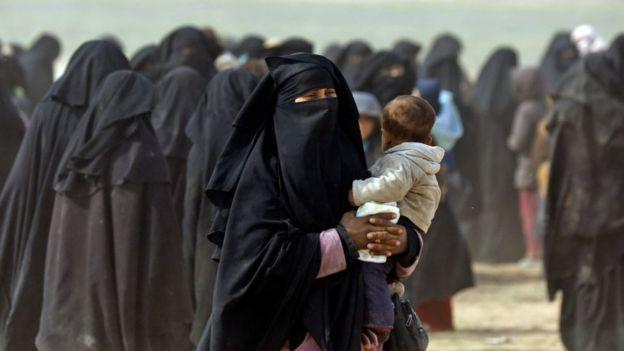 Mujer escapando con su hijo de un territorio que era controlado por el EI.