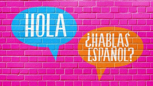 Hola y ¿Hablas español? escritos en una pared.