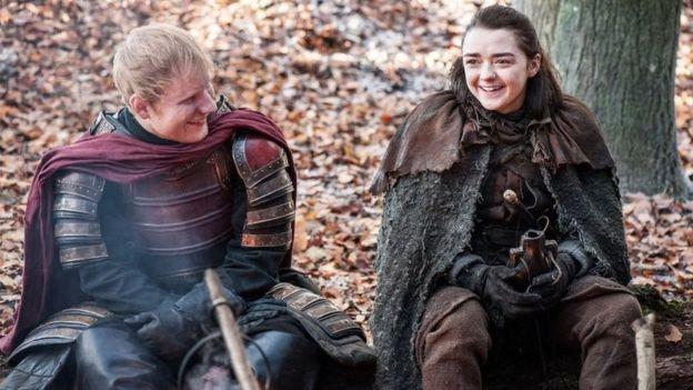 Foto de folheto não datada emitida pela HBO de Ed Sheeran que olha no drama de TV Game of Thrones, ao lado de Maisie Williams, que interpreta Arya Stark.