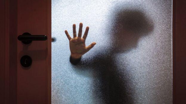 Niño con mano en la puerta