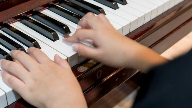 Close up child playing piano