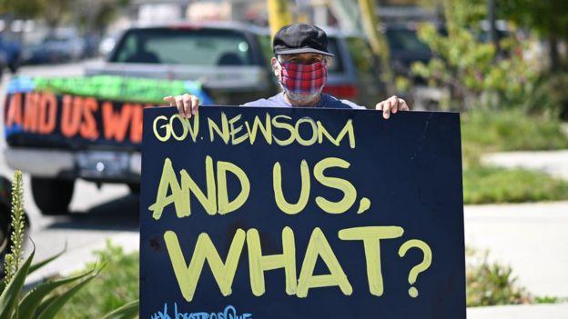 Un hombre con un cartel dirigido al gobernador de California en el que le pregunta: ¿Y nosotros qué?