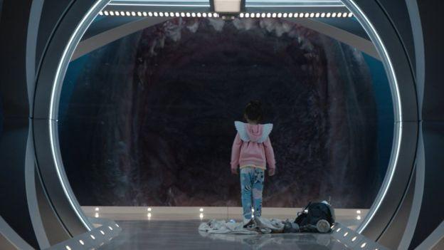 เด็กยืนอยู่หน้ากระจกที่ฉลามอ้าปาก