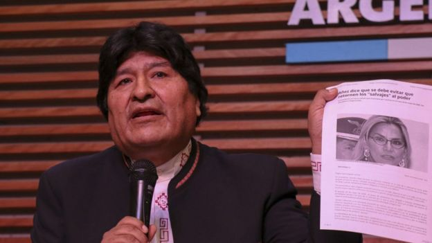 Evo Morales sosteniendo un artículo con una foto de Jeanine Áñez.