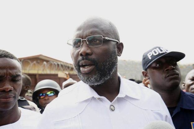 George Weah (C) leaves a polling station after casting his ballot in Monrovia, Liberia, 26 December 2017