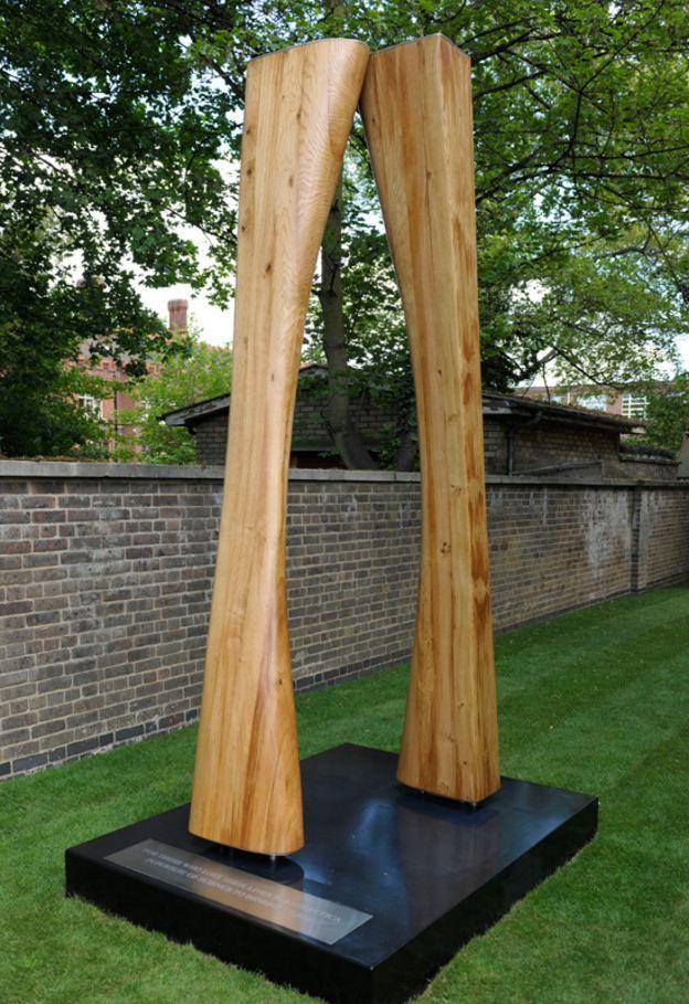 Dos grandes pilares de roble curvos que se tocan apenas en la parte superior