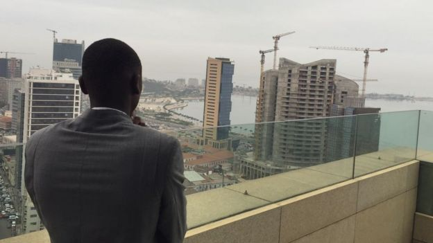 Half-built skyscrapers in Luanda, as a man in a suit looks on