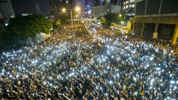 Protestors and student demonstrators hold up their cellphones in a display of solidarity during a protest outside the headquarters of Legislative Council in Hong Kong on 29 September 2014
