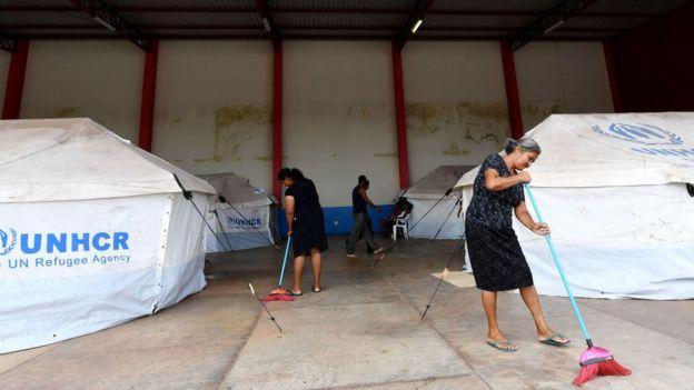 Mulheres varrem o chão em acampamento para venezuelanos no Brasil