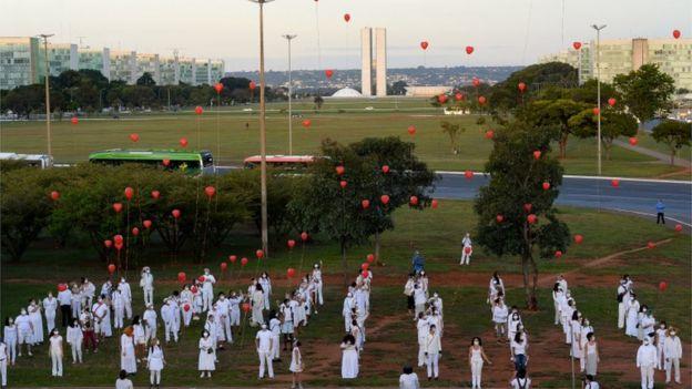 Em demonstração em área aberta de Brasília, diversas pessoas em filas vestidas de branco soltam balões vermelhos em homenagem a vítimas da covid-19