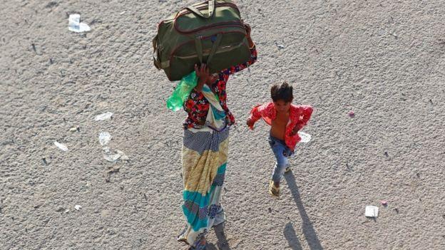 Una mujer india y su hijo viajan a su aldea natal en medio de la pandemia.