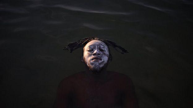 Rosto ensaboado de Ali na superfície da água