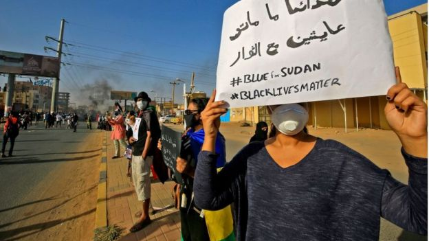 "A Sudanese protester holds up a sign reading in Arabic ""our martyrs are not dead, they are alive with the revolutionaries"" along with the English slogans ""#BLUEforSUDAN"" and ""#BLACKLIVESMATTER"", as demonstrators mark the first anniversary of a raid on an anti-government sit-in and some demonstrate in support of US protesters over the death of George Floyd, in the Riyadh district in the east of the capital Khartoum on June 3, 2020"