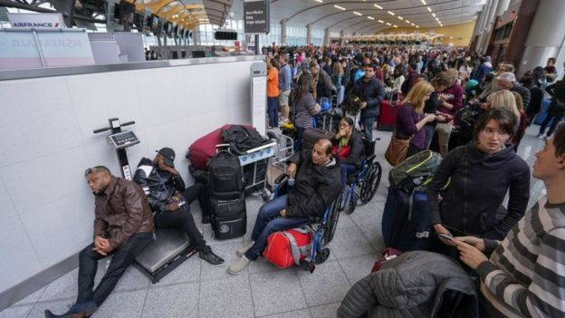 Passengers affected by widespread power outage sit in airport terminal and wait for updates