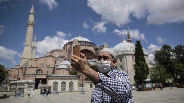 رجل يرتدي كمامة يلتقط صورة لنفسه مع آيا صوفيا في الخلفية