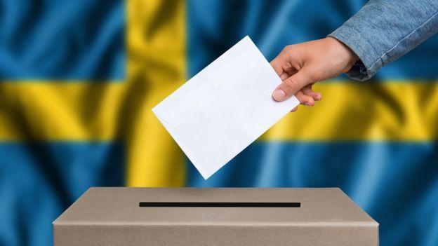 Urna de votación con bandera sueca de fondo.