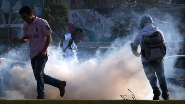 Venezuelans run away from tear gas during scuffles with security forces in Caracas on April 30, 2019. - Venezuelan opposition leader and self-proclaimed acting president Juan Guaido said on Tuesday that troops had joined his campaign to oust President Nicolas Maduro as the government vowed to put down what it said was an attempted coup.