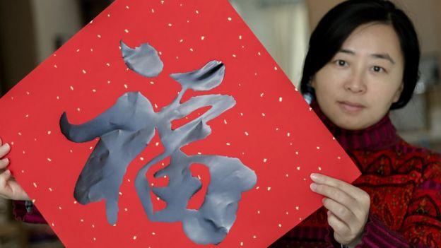 Una mujer con un sobre rojo