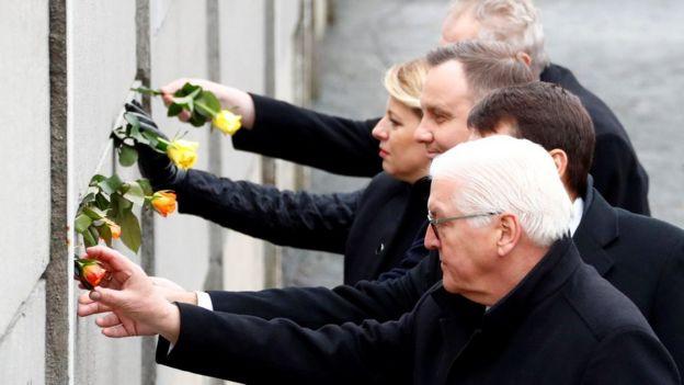 German President Frank-Walter Steinmeier, Hungary's President Janos Ader, Poland's President Andrzej Duda, Slovakia's President Zuzana Caputova and Czech Republic's President Milos Zeman place roses into a gap at the Wall memorial