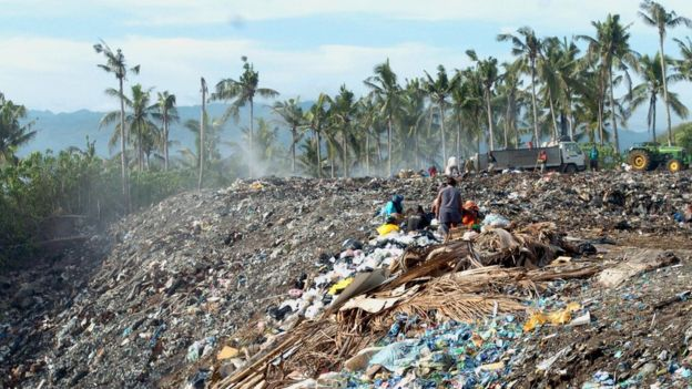 Scavengers sift through the piles of garbage that have been dumped on a hillside in the central Philippine resort island of Boracay