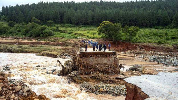 Grupo de personas sobre carretera destruida en Zimbabue.