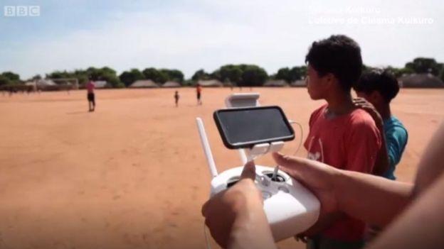 Jóvenes kuikuro manejando un drone.