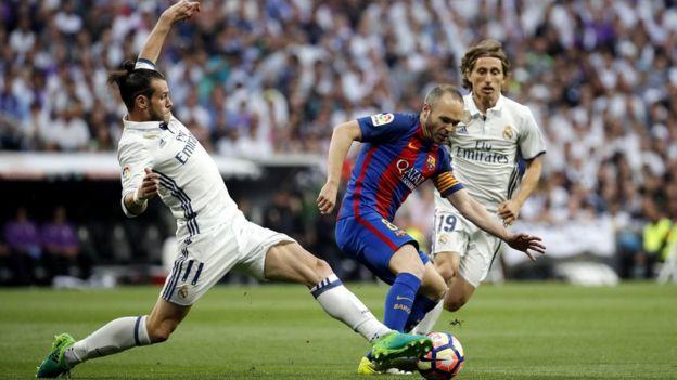 Iniesta maniobra con la pelota entre Modric y Bale.