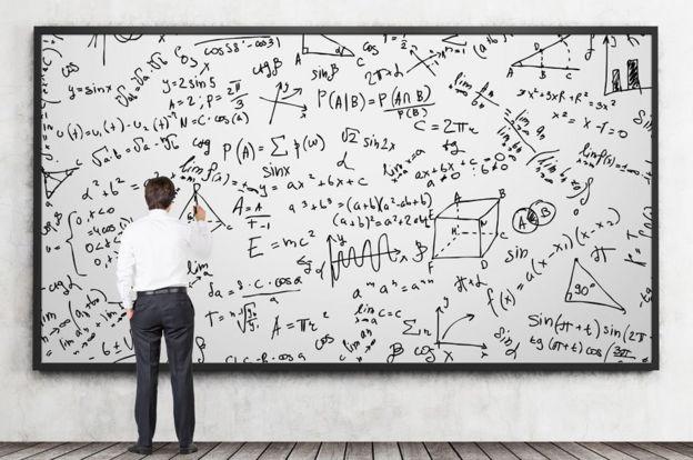 Un hombre escribiendo fórmulas en un pizarrón.