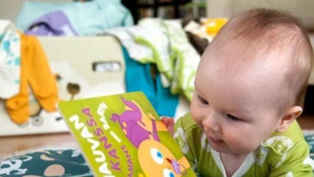 Bebé con un librito (Foto: Kela)