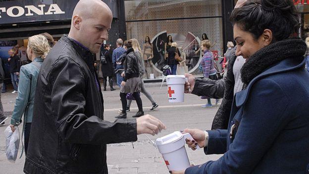 Personas recogiendo donaciones para la cruz roja danesa.