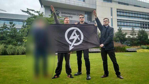 Chad Williams-Allen, Daniel Bogunovic e Alex Deakin posam com bandeira do Ação Nacional