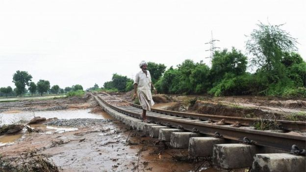 In this photograph taken July 29, 2017 an Indian villager walks along damaged railway tracks due to floods at Godha village of Deesa taluka, some 195km from Ahmedabad.