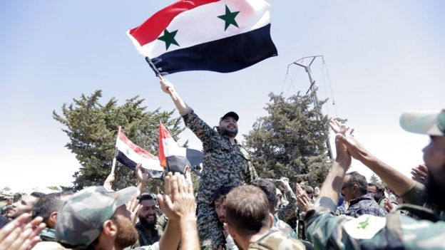 Syrian soldiers wave the Syrian national flag in the city of Quneitra, in the Golan Heights (27 July 2018)
