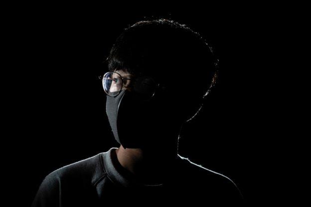 صورة لمتظاهر في هونغ كونغ نصف وجهه طوليا مظلم والنصف الآخر مضيء