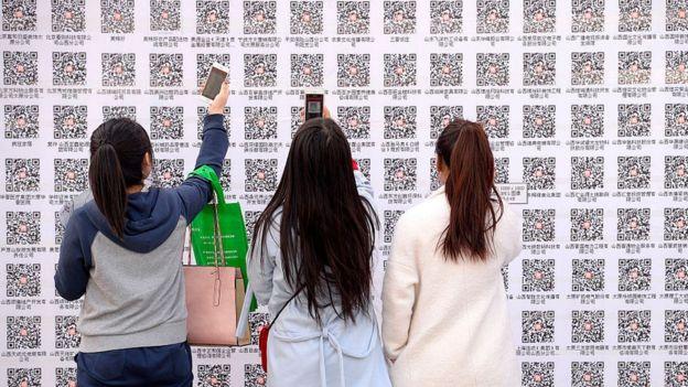 jóvenes leyendo un código QR a través de su teléfono móvil.