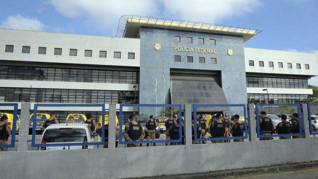 Prédio da Polícia Federal em Curitiba, com agentes e viaturas em frente