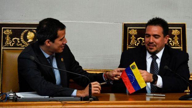 El diputado Stalin González (der.) recibe una pequeña bandera de Venezuela de manos de Juan Guaidó.