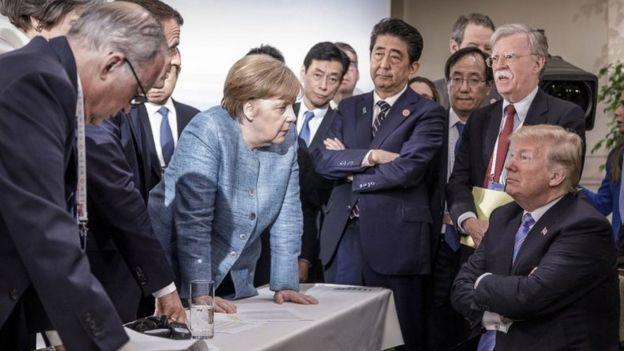 Líderes en el G7 mirando a Trump sentado.