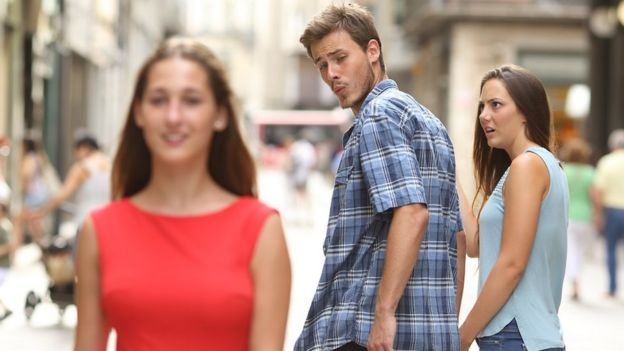 Disloyal man walking with his girlfriend and looking amazed at another girl