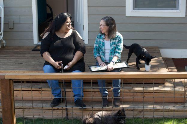 Sherry Mesa (E) sentada com Martha Chambers (D) e um cachorro ao lado, em frente à microcasa em que vive com a sobrinha nos EUA